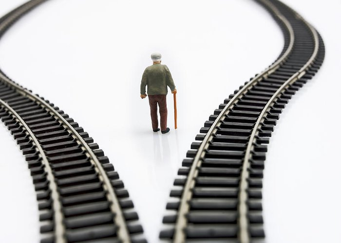 Stick Greeting Card featuring the photograph Figurine Between Two Tracks Leading Into Different Directions Symbolic Image For Making Decisions. by Bernard Jaubert