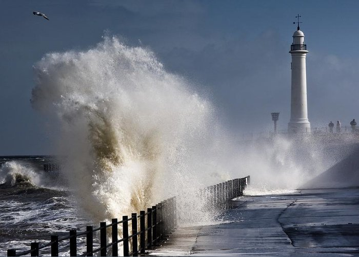 Building Exterior Greeting Card featuring the photograph Waves Crashing By Lighthouse At by John Short