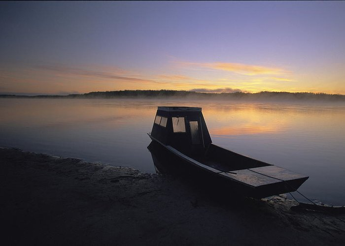 Boats Greeting Card featuring the photograph A Boat Sits On The Calm Yukon River by Michael Melford