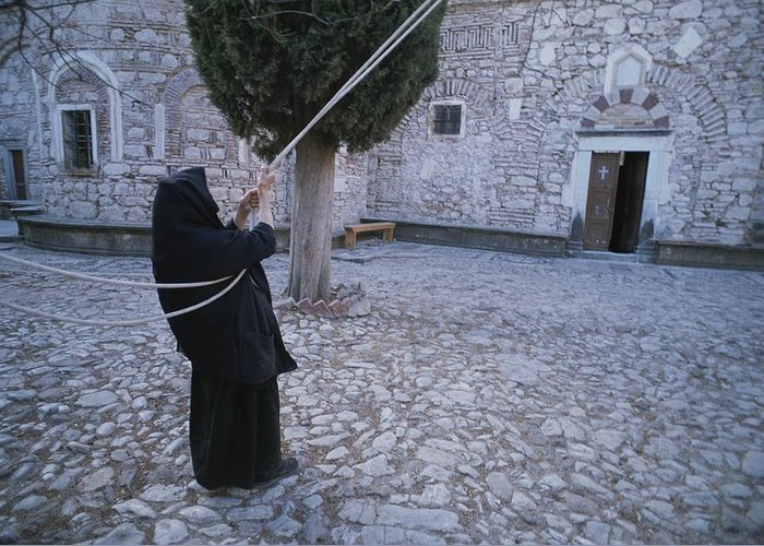 Europe Greeting Card featuring the photograph A Nun Pulls On Ropes In A Courtyard by Tino Soriano