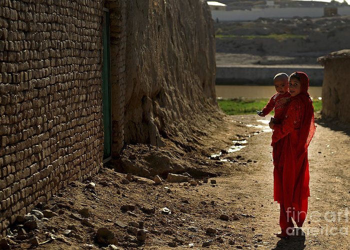 Qalat Greeting Card featuring the photograph An Afghan Girl Carries Her Little by Stocktrek Images