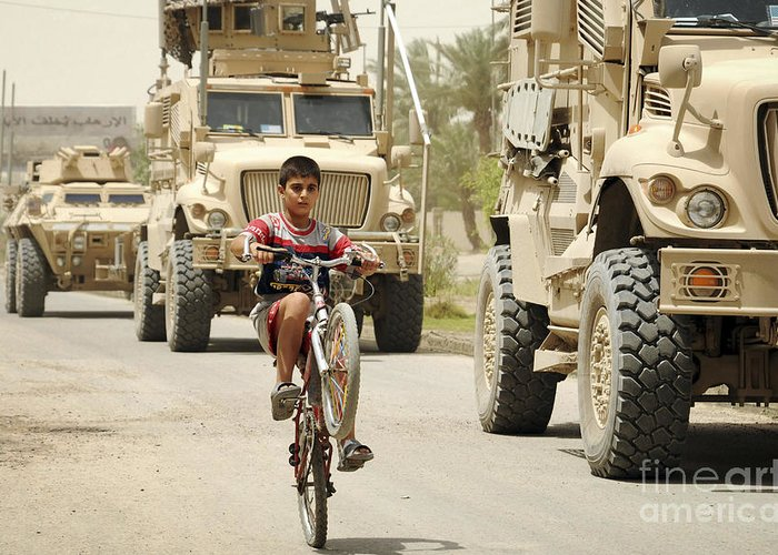 Military Greeting Card featuring the photograph An Iraqi Boy Rides His Bike Past A U.s by Stocktrek Images