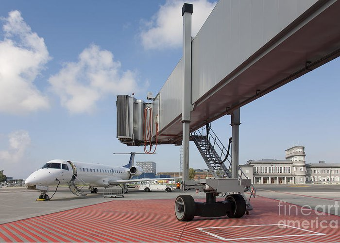Air Travel Greeting Card featuring the photograph Boarding Bridge Leading To A Parked Plane by Jaak Nilson
