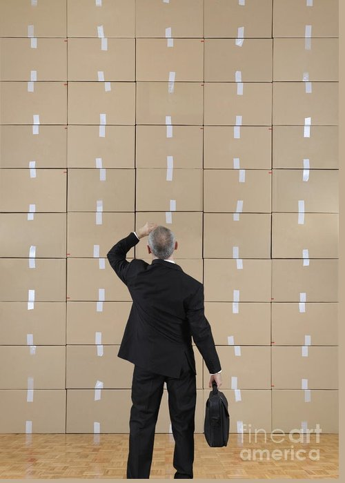 Facing Greeting Card featuring the photograph Businessman Facing A Cardboard Boxes Wall by Sami Sarkis