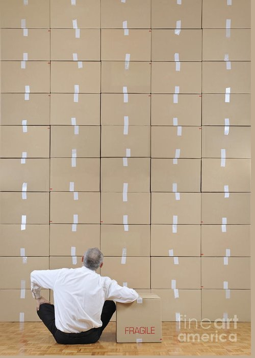 Facing Greeting Card featuring the photograph Businessman Seated Facing Cardboard Boxes Wall by Sami Sarkis