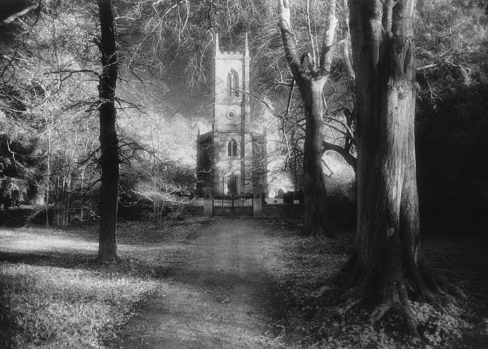 Eerie; Atmospheric; Spooky; Country Lane; Track; Approach; Wooded; Facade; Clock Tower; Exterior; Architecture; English; Spooky; Haunting; Haunted; Mysterious; Dramatic; Gothic Greeting Card featuring the photograph Church Of St Mary Magdalene by Simon Marsden