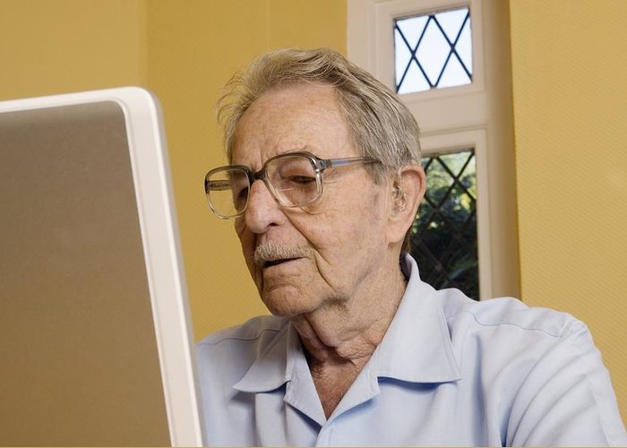 Laptop Greeting Card featuring the photograph Elderly Man Using A Laptop Computer by Steve Horrell