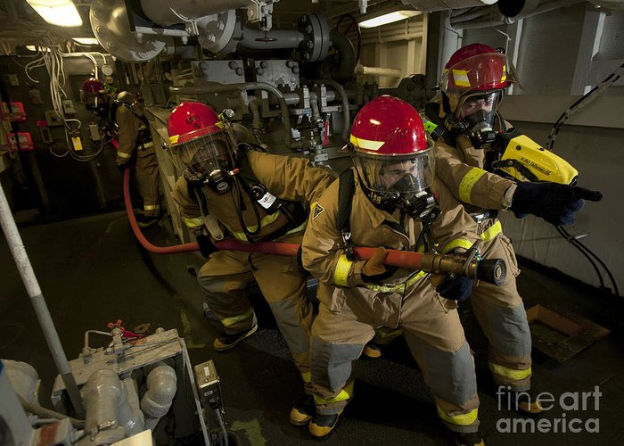 Warship Greeting Card featuring the photograph Firemen Combat A Simulated Fire Aboard by Stocktrek Images