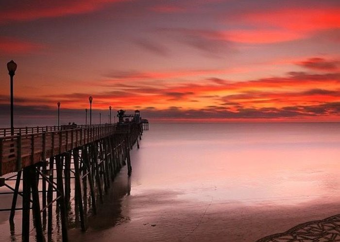 All_sunsets Greeting Card featuring the photograph Long Exposure Sunset At The Oceanside by Larry Marshall