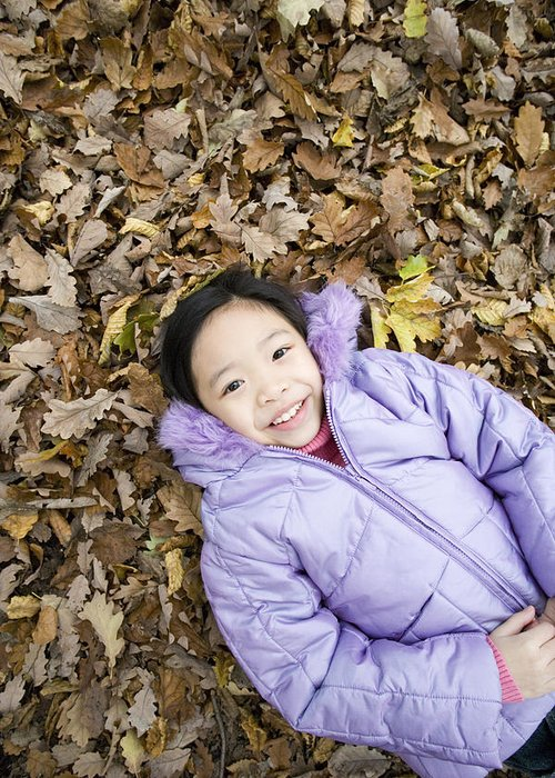 Human Greeting Card featuring the photograph Smiling Girl Lying On Autumn Leaves by Ian Boddy