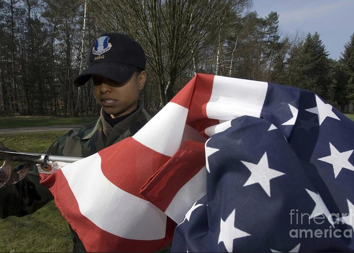 Horizontal Greeting Card featuring the photograph Soldier Unfurls A New Flag For Posting by Stocktrek Images