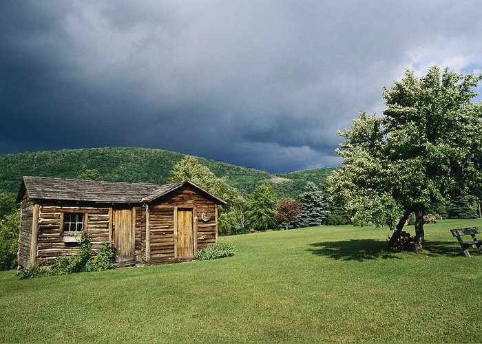 North America Greeting Card featuring the photograph Storm Clouds Form Above A Log Cabin by Raymond Gehman