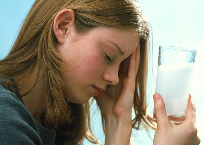 Dissolving Greeting Card featuring the photograph Teenager With Headache Holds Dissolving Painkiller by Damien Lovegrove