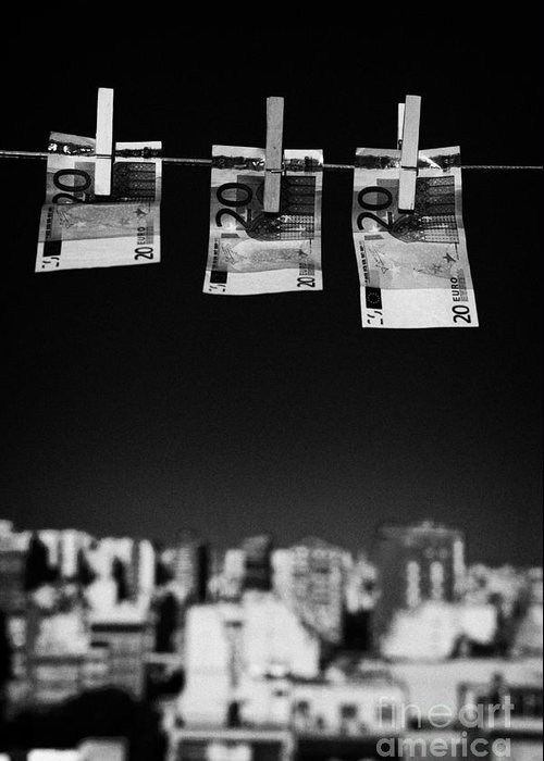 Money Greeting Card featuring the photograph Three Twenty Euro Banknotes Hanging On A Washing Line With Blue Sky Over City Skyline by Joe Fox