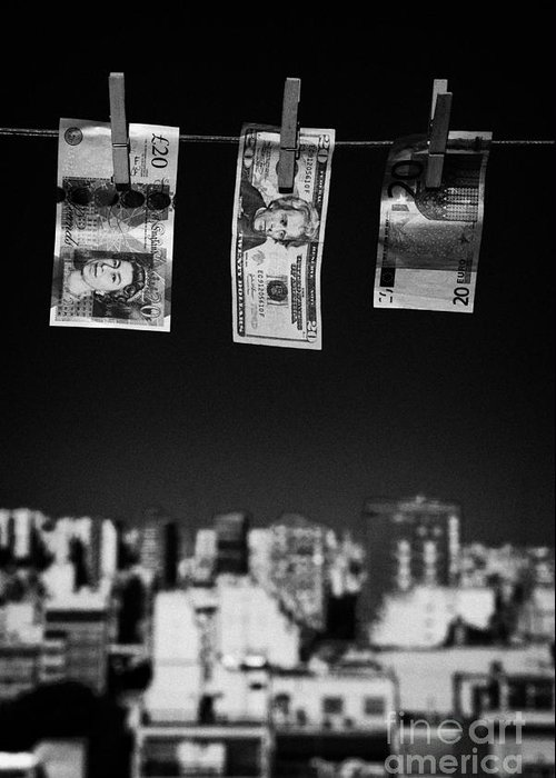 Money Greeting Card featuring the photograph Twenty Pounds Dollars Euro Banknotes Hanging On A Washing Line With Blue Sky Over City Skyline by Joe Fox