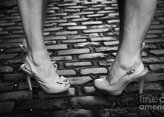 Two Greeting Card featuring the photograph Two Young Women Wearing High Heeled Shoes And Fake Tan On Cobblestones On A Night Out by Joe Fox