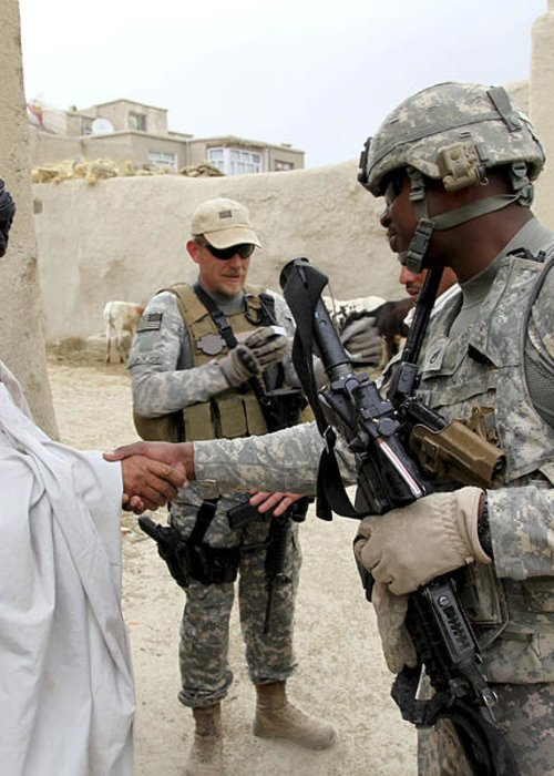 Middle East Greeting Card featuring the photograph U.s. Army Soldier Shakes Hands With An by Stocktrek Images