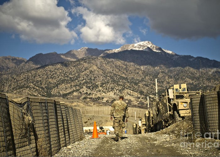Military Greeting Card featuring the photograph U.s. Army Soldier Walks Down A Path by Stocktrek Images