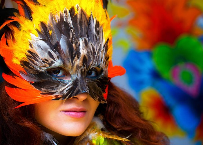 Woman Greeting Card featuring the painting Young Woman With A Colorful Feather Carnival Face Mask On Bright Colorful Background Eye Contact by Jozef Klopacka