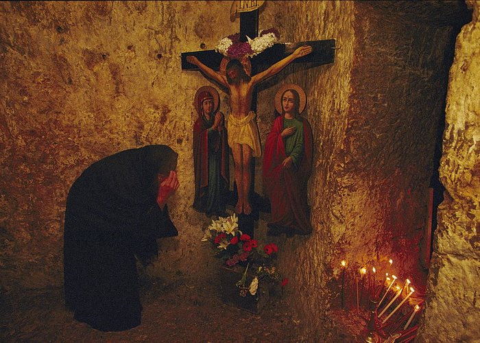 Color Image Greeting Card featuring the photograph A Greek Pilgrim Prays In The Grotto by Annie Griffiths