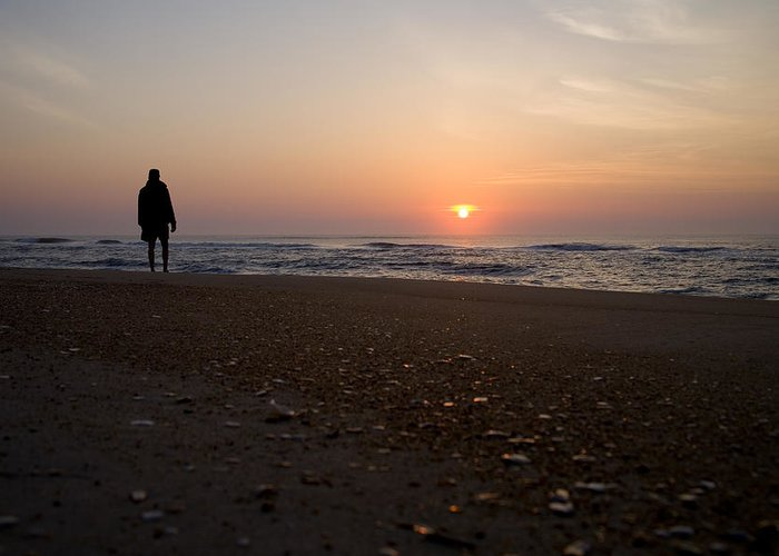 Avon Hatteras Island Greeting Card featuring the photograph A Lone Figure Enjoys The Ocean Sunrise by Stephen St. John