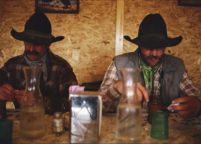 Model Released Photography Greeting Card featuring the photograph A Pair Of Cowboys Enjoy A Cup Of Coffee by Joel Sartore