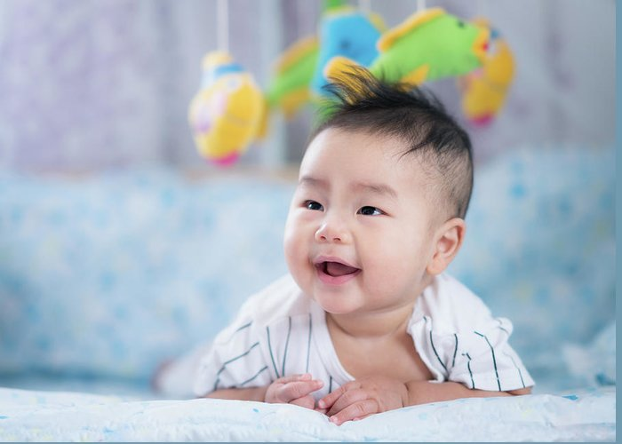 Baby Greeting Card featuring the photograph Asian Newborn Baby Smile In A Bed With Fish And Animal Mobile by Anek Suwannaphoom