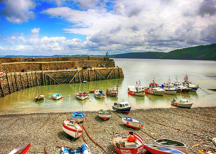 Harbor; Breakwater; Boats; Clovelly; North; Devon; Buildings; Steep; Hill; Hillside; Coastal; Coastline; Architecture; Historical; Place; Fishing; Village; Landmark; Summer; Tourist; Trade; Travel; Tourism; Popular; Location; Quaint; Picturesque; Old; Historic; English; England; Gb; Uk Greeting Card featuring the photograph Boats In The Harbor At Clovelly In Devon by Chris Smith