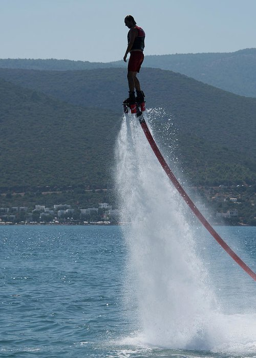 Bodrum Greeting Card featuring the photograph Flyboarder In Silhouette Balancing High Above Water by Ndp