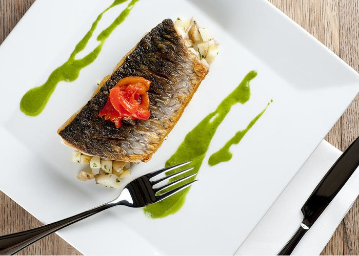 Grey Mullet Greeting Card featuring the photograph Grey Mullet With Watercress Sauce Presented On A Square White Plate With Cutlery And Napkin by Andy Smy