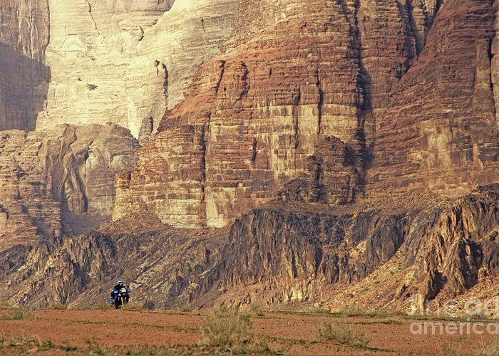 Alone Greeting Card featuring the photograph Person Riding A Motorbike Through The Wadi Rum Desert In Jordan by Sami Sarkis