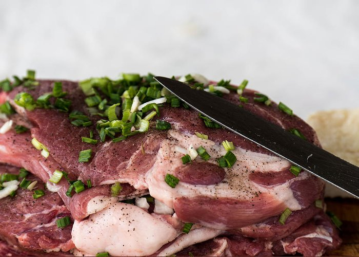 Background Greeting Card featuring the photograph Pork meat with green garlik and knife by Adrian Bud