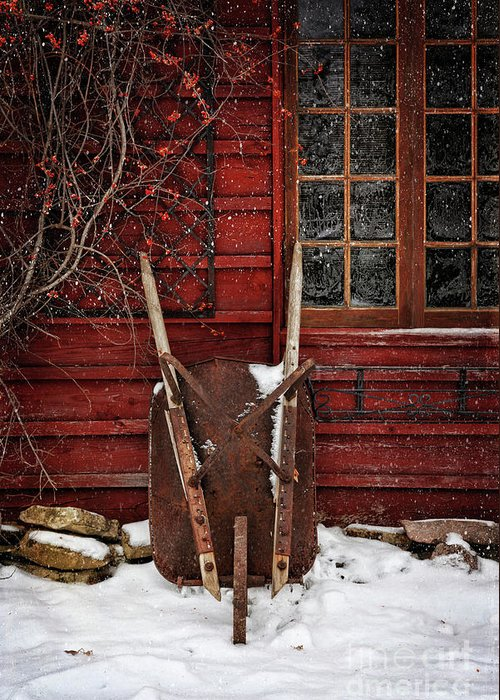 Atmosphere Greeting Card featuring the photograph Rusty Wheelbarrow Leaning Against Barn In Winter by Sandra Cunningham