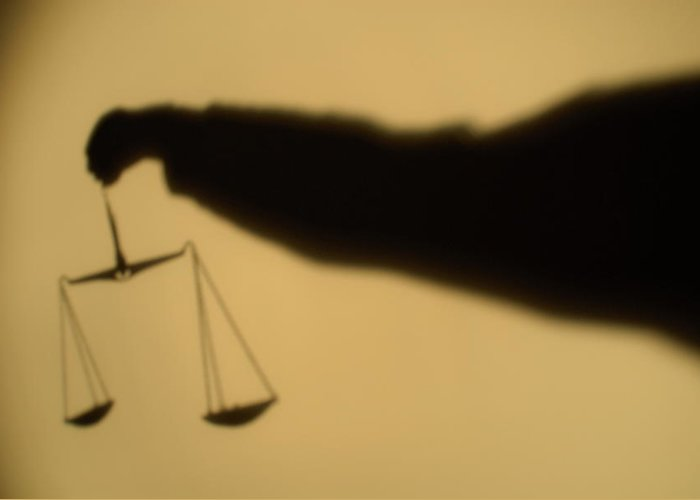 Arm Greeting Card featuring the photograph Shadow Of A Person's Arm Holding Out The Scales Of Justice by Sami Sarkis
