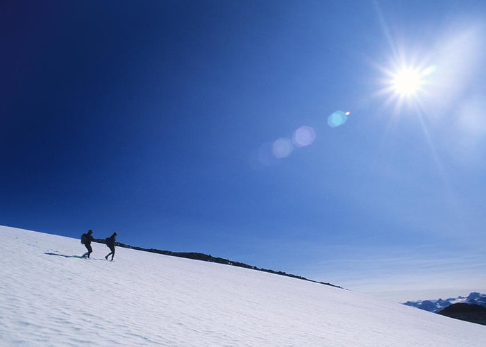 Two People Greeting Card featuring the photograph Two Hikers Explore A Snowfield by Bill Hatcher
