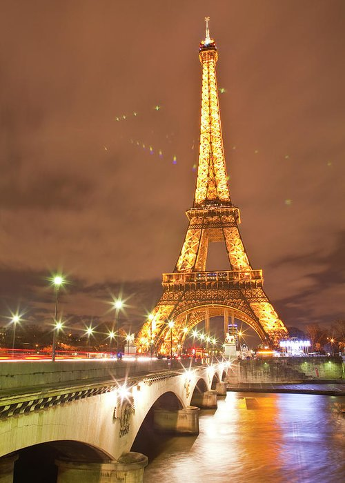 In A Row Greeting Card featuring the photograph The Eiffel Tower Lit Up At Night In by Julian Elliott Photography