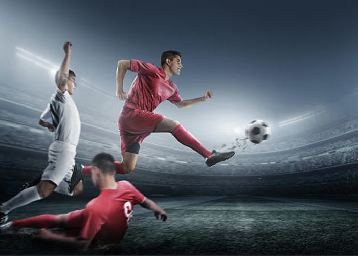 Soccer Uniform Greeting Card featuring the photograph Soccer Player Kicking Ball In Stadium by Dmytro Aksonov