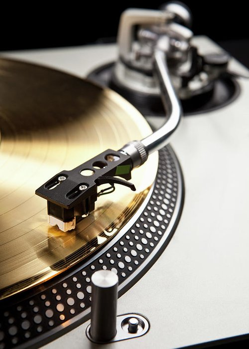 Music Greeting Card featuring the photograph A Gold Record On A Turntable by Caspar Benson