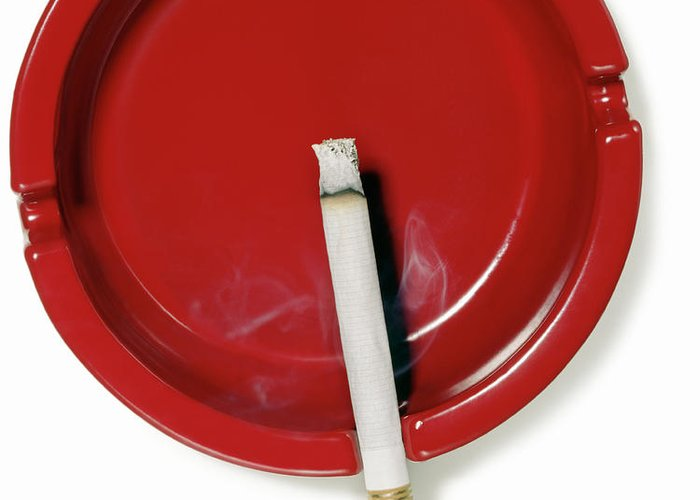 White Background Greeting Card featuring the photograph A Red Ashtray With A Burning Cigarette by Steve Wisbauer