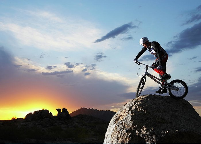 Sports Helmet Greeting Card featuring the photograph Bike Rider Balancing On Rock Boulder by Thomas Northcut