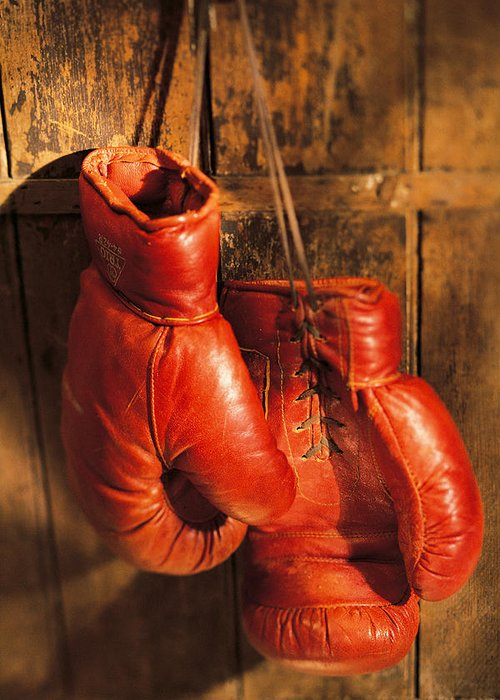 Hanging Greeting Card featuring the photograph Boxing Gloves Hanging On Rustic Wooden by Comstock