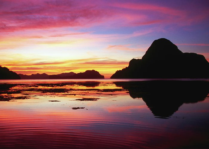 Scenics Greeting Card featuring the photograph Cadlao Island Silhouetted At Sunset by Dallas Stribley