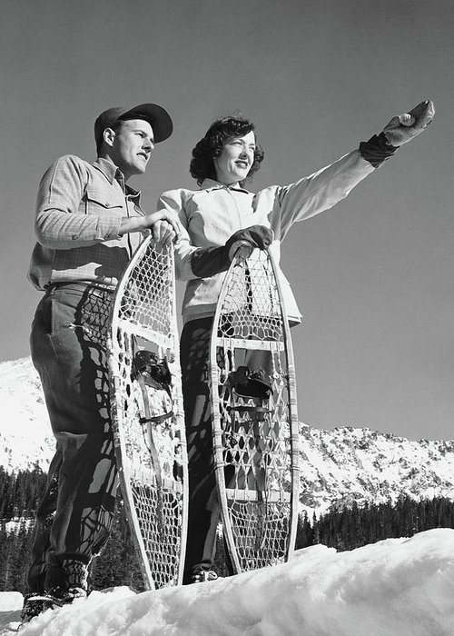 Heterosexual Couple Greeting Card featuring the photograph Couple Holding Snowshoes, Woman Pointing by Stockbyte
