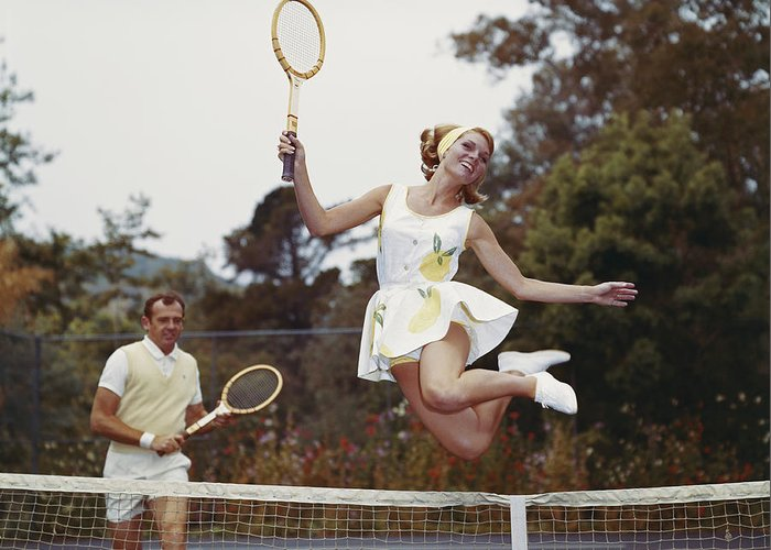 Heterosexual Couple Greeting Card featuring the photograph Couple On Tennis Court, Woman Jumping by Tom Kelley Archive
