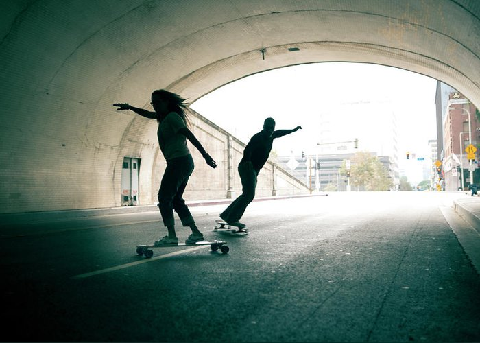 Mature Adult Greeting Card featuring the photograph Couple Skateboarding Through Tunnel by Ian Logan