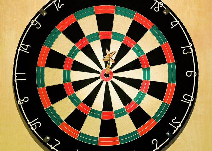 Expertise Greeting Card featuring the photograph Dart In Bulls Eye On Dart Board by Fuse