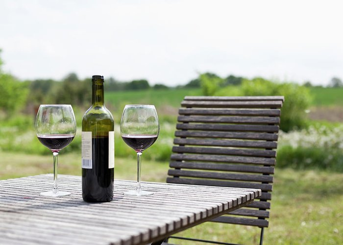 Five Objects Greeting Card featuring the photograph Glasses And A Bottle Of Red Wine On An by Halfdark