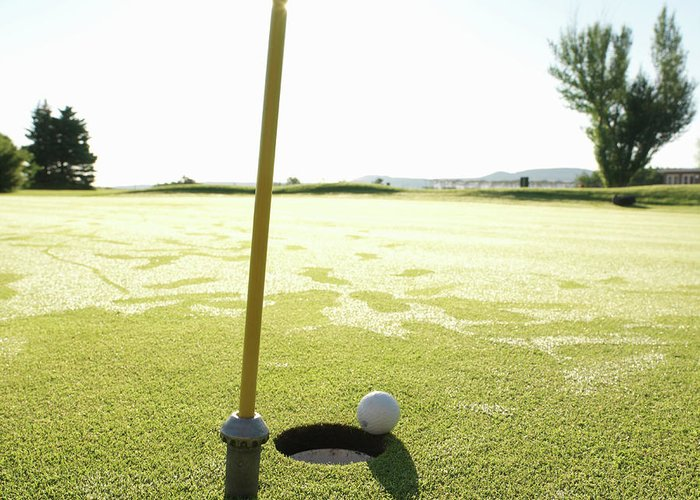 Grass Greeting Card featuring the photograph Golf Ball Near Hole At Sunrise, High by Ascent/pks Media Inc.