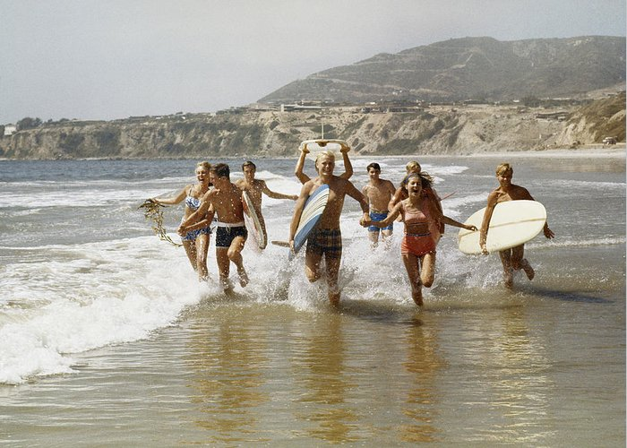 Young Men Greeting Card featuring the photograph Group Of Surfers Running In Water With by Tom Kelley Archive