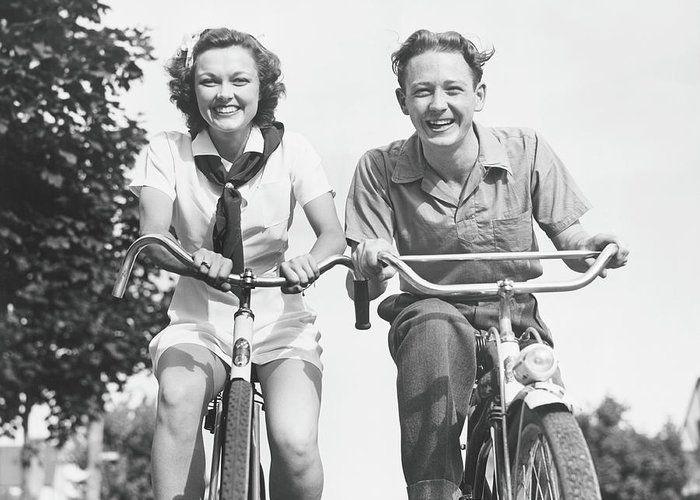 Young Men Greeting Card featuring the photograph Man And Woman Riding Bikes, B&w, Low by George Marks